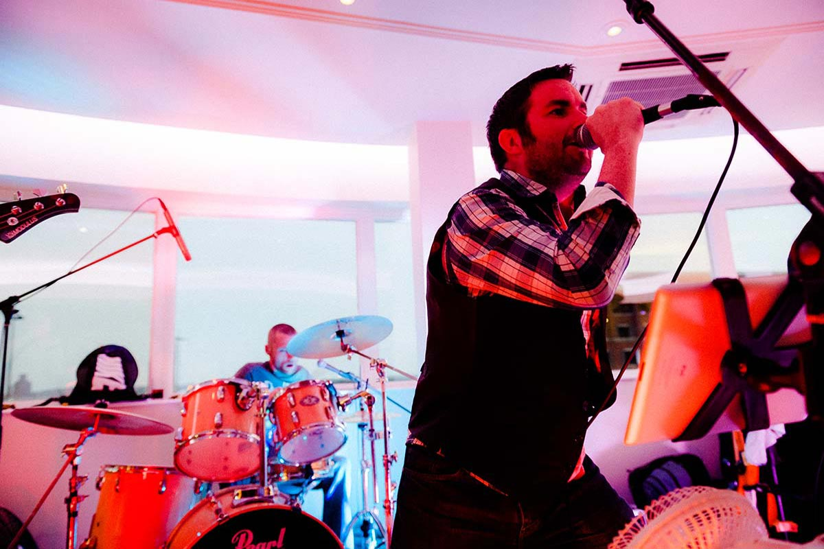Live Wedding Band Slinky | Rock Pop and Indie Wedding Band | The singer performing at a wedding reception.