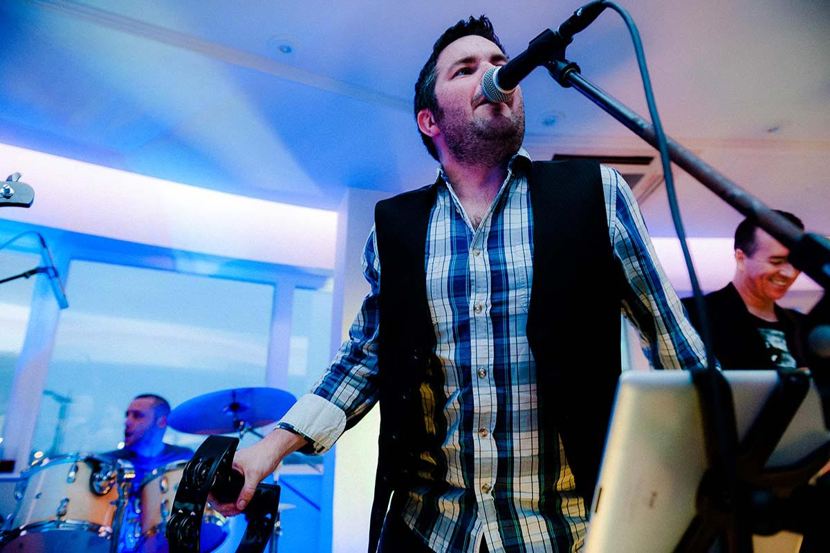 Live Wedding Band Slinky | Rock Pop and Indie Wedding Band | The singer making use of a tambourine whilst singing at a wedding reception