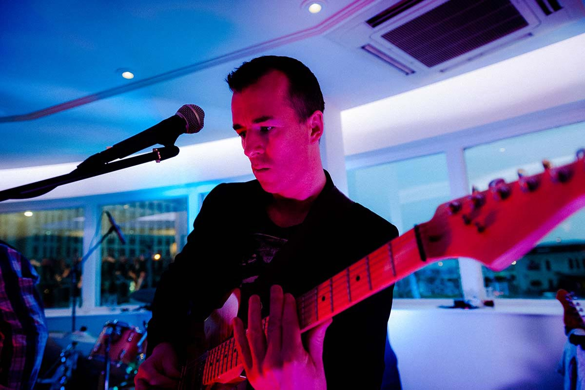 Live Wedding Band Slinky | Rock Pop and Indie Wedding Band | The guitarist performing at a wedding reception.