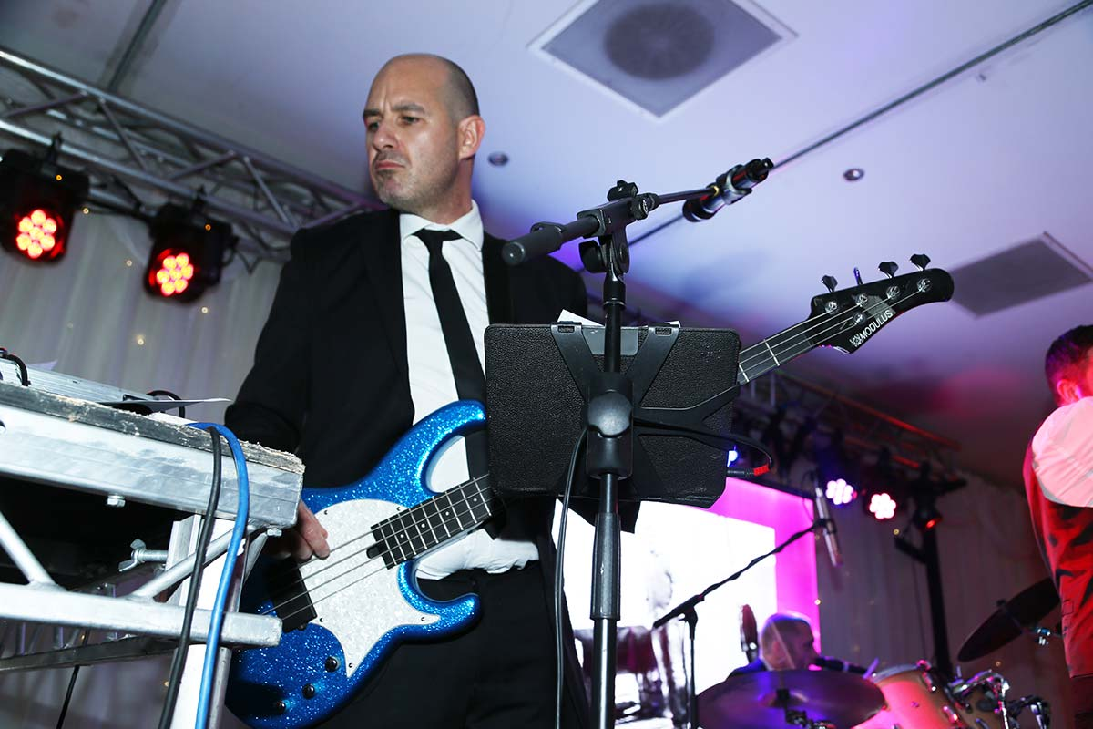 Live Wedding Band Slinky | Rock Pop and Indie Wedding Band | Bassist performing at a corporate event.