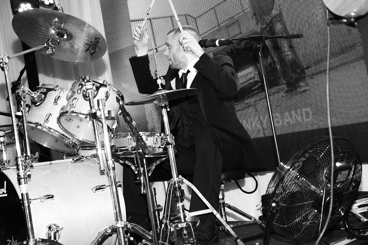 Live Wedding Band Slinky | Rock Pop and Indie Wedding Band | Drummer performing at a corporate event.