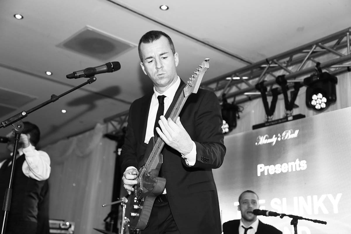 Live Wedding Band Slinky | Rock Pop and Indie Wedding Band | Guitarist performing at a corporate event.