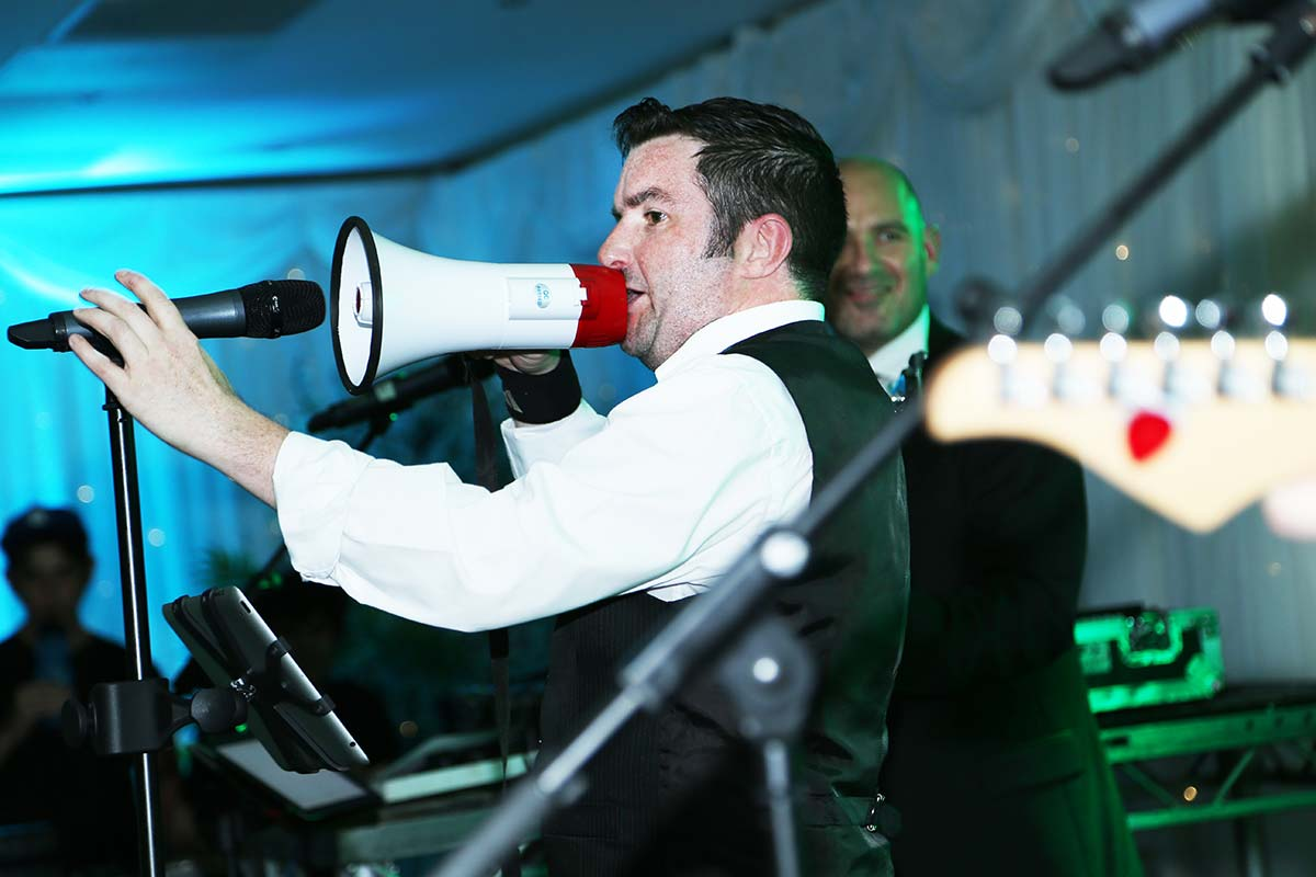 Live Wedding Band Slinky | Rock Pop and Indie Wedding Band | Singer performing with a megaphone at a corporate event.