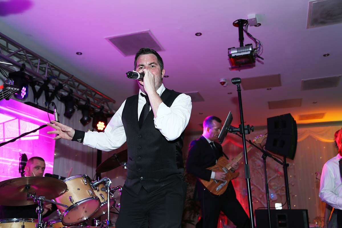 Live Wedding Band Slinky | Rock Pop and Indie Wedding Band | Singer on mic performing at a corporate event.
