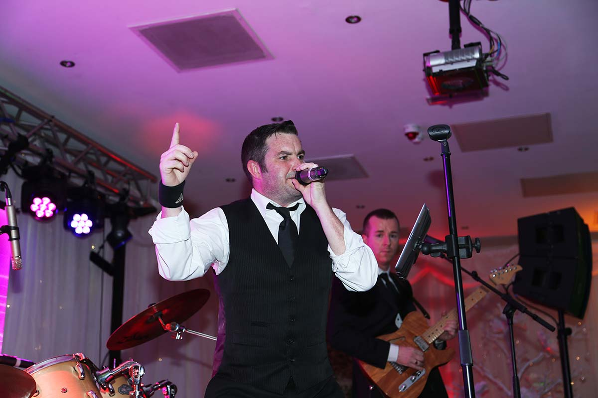 Live Wedding Band Slinky | Rock Pop and Indie Wedding Band | Singer giving the audience a cue at a corporate event.