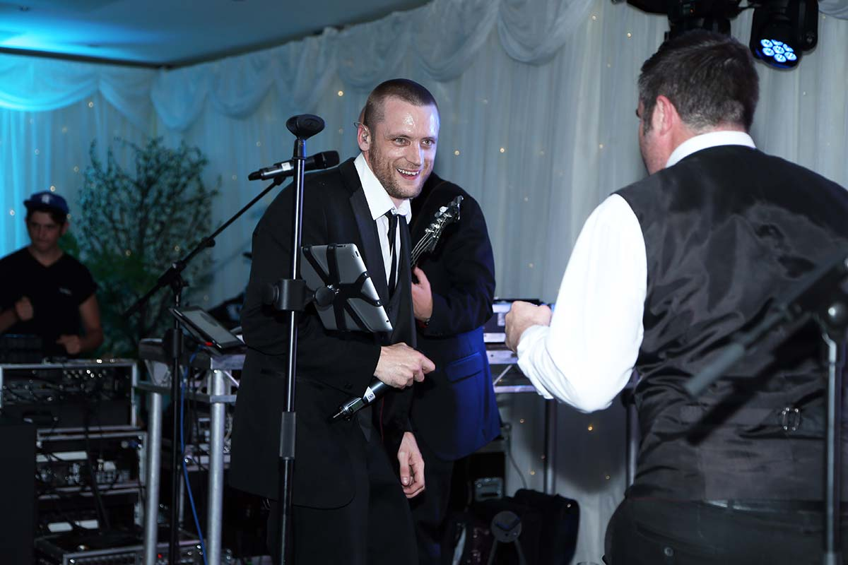 Live Wedding Band Slinky | Rock Pop and Indie Wedding Band | The singer and drummer have a laugh on stage at a corporate event.