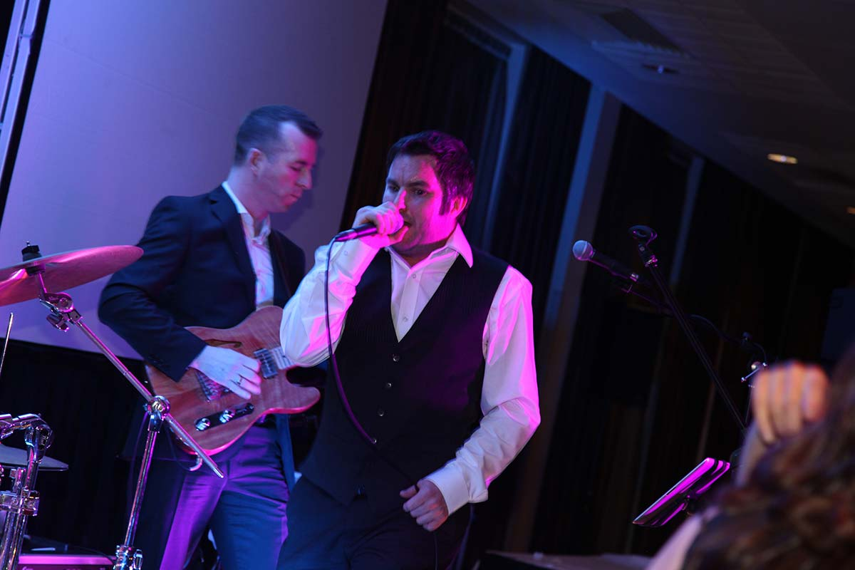 Live Wedding Band Slinky | Rock Pop and Indie Wedding Band | Singer and guitarist performing at birthday party.