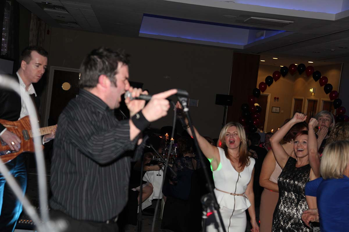 Live Wedding Band Slinky | Rock Pop and Indie Wedding Band | Singer leads the audience in song at birthday party.