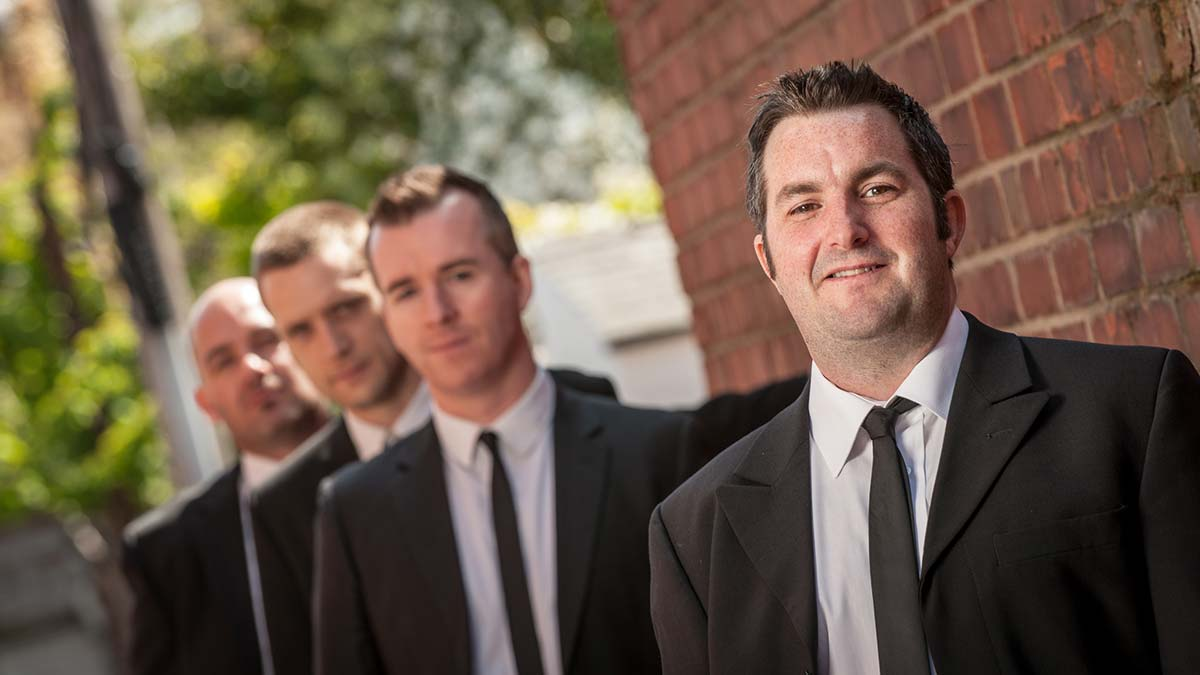 Live Wedding Band Slinky | Rock Pop and Indie Wedding Band | Band head shot in a row in front of a brickwall.