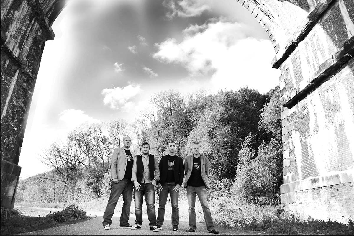 Live Wedding Band Slinky | Rock Pop and Indie Wedding Band | Band stood underneath an aqueduct.