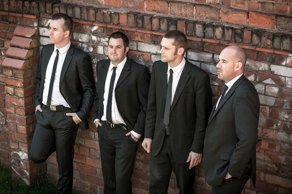 Live Wedding Band Slinky | Rock Pop and Indie Wedding Band | Band wearing suits in against a brickwall.