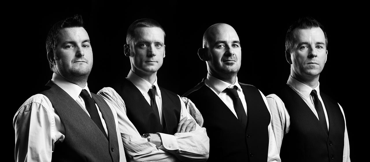 Live Wedding Band Slinky | Rock Pop and Indie Wedding Band | Band wearing waistcoats in studio against a black backdrop.