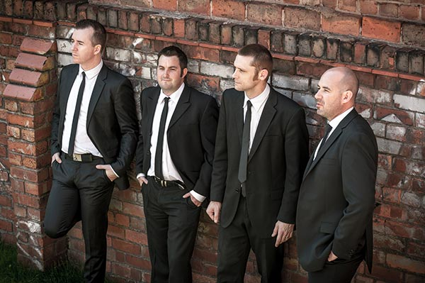 Wedding Music Band Slinky | Band Hire | Manchester | Yorkshire | Band shot in smart suits by a wall.