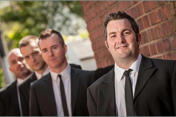 Wedding Music Band Slinky | Band Hire | Manchester | Yorkshire | Band shot in smart suits by a wall, looking up