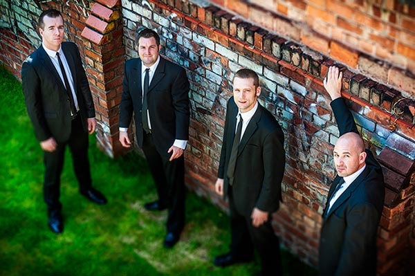 Wedding Music Band Slinky | Band Hire | Manchester | Yorkshire | Band shot in smart suits by a wall, looking up.